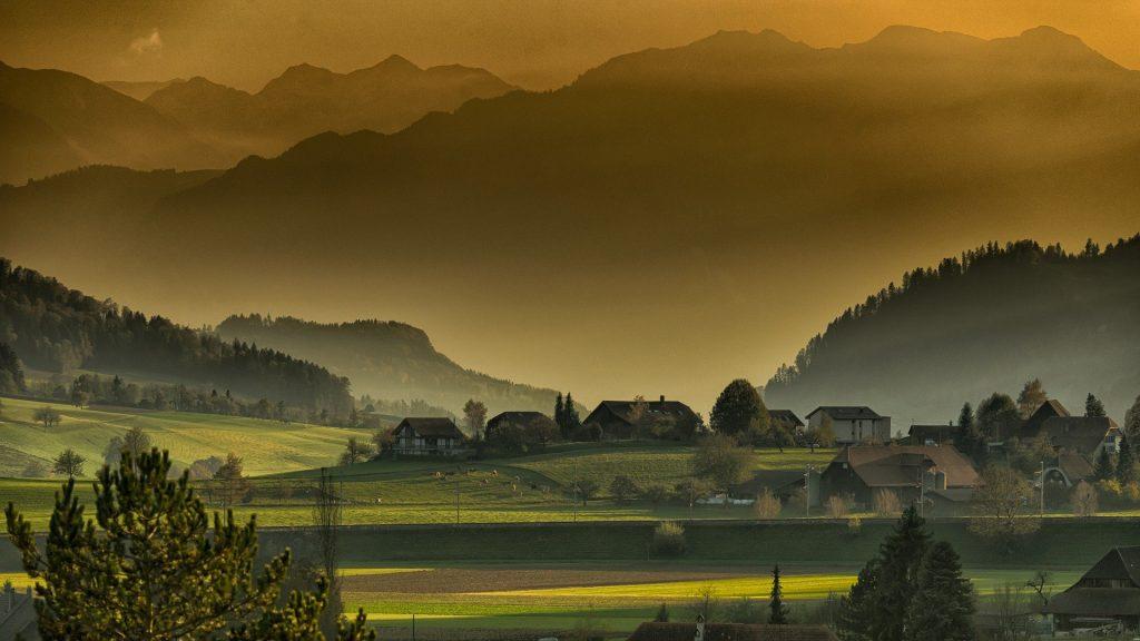 Een Toscane-achtig herfstlandschap. De kenmerkende rustige heuvels, afgewisseld met hoge bergen. De zon schijnt er prachtig geel doorheen, wat een erg mooi effect heeft op het groene gras.