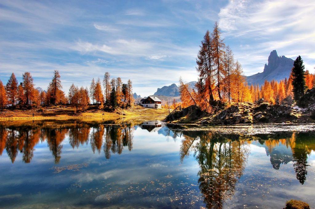 Een prachtig Noorweegs uitzicht met een typisch huis in het midden van het beeld, kenmerkend aan de witte en rode muren. De mooie oranje bomen op het land, waarvoor een mooie weerspiegeling in het meer te zien is. Op de achtergrond liggen bijzondere puntige bomen.