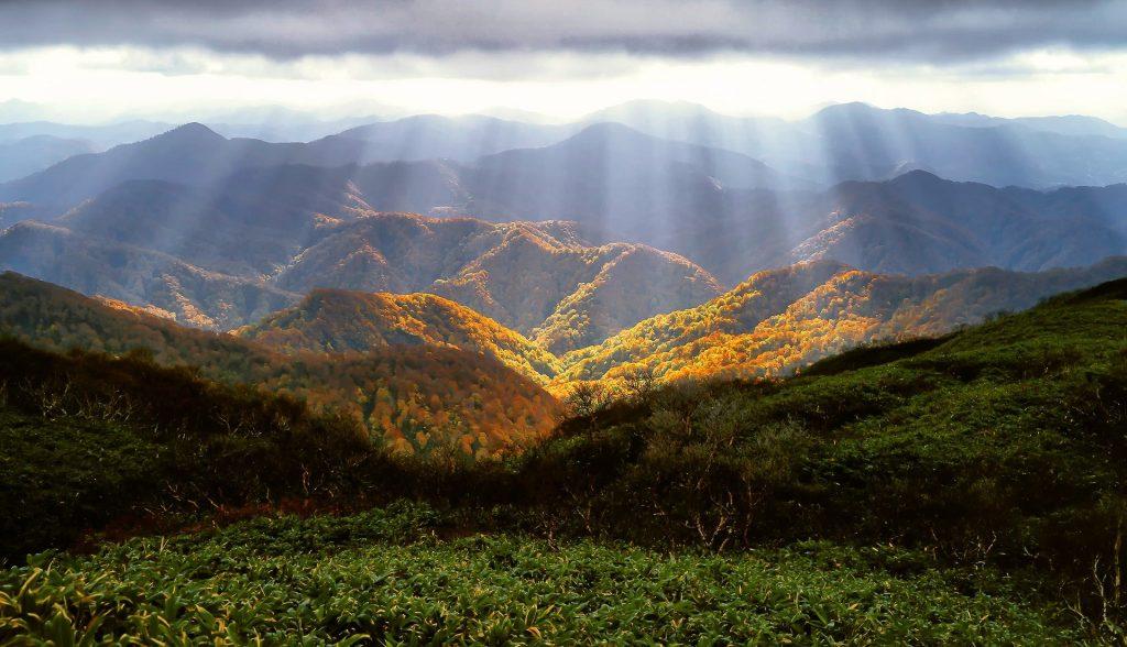 Het zonlicht wat op de regen schijnt is iets unieks. Je kijkt uit op een kilometers ver heuvellandschap. Het licht op de bomen maakt de bomen mooi geel en groen.