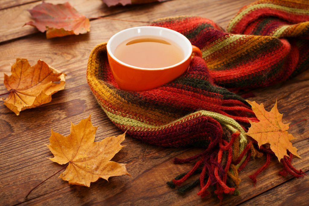 Een lekkere, warme thee in een oranje mok, perfect passend bij het herfstthema. Gewikkeld in een sjaal in prachtige herfstkleuren. Op een houten tafel, gesierd door unieke herfstbladeren.