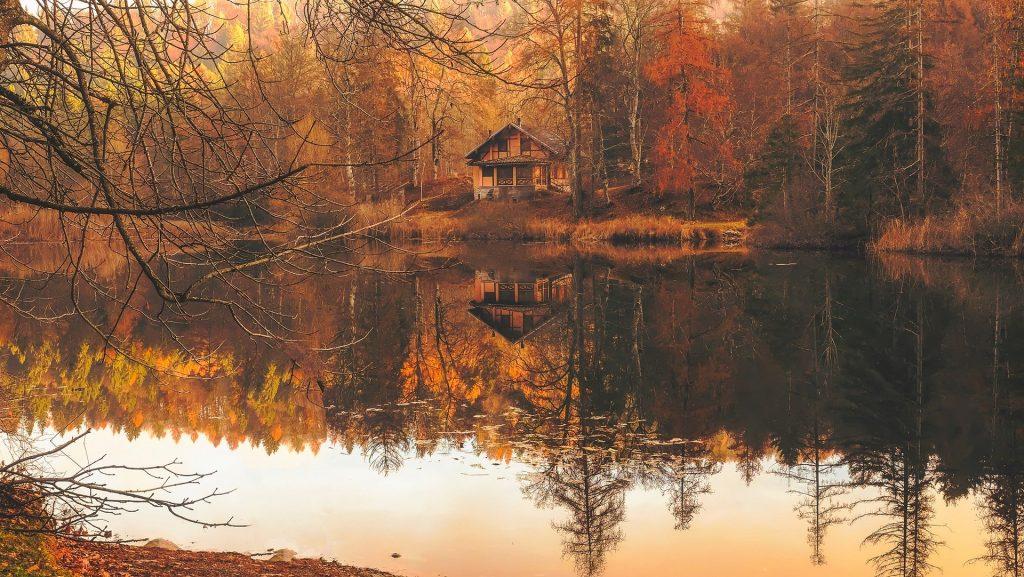 Een bijzonder mooi houten blokhutje aan een afgelegen bosmeertje. Het meer zorgt voor een prachtige weerspiegeling van het huis en de omgelegen bomen.