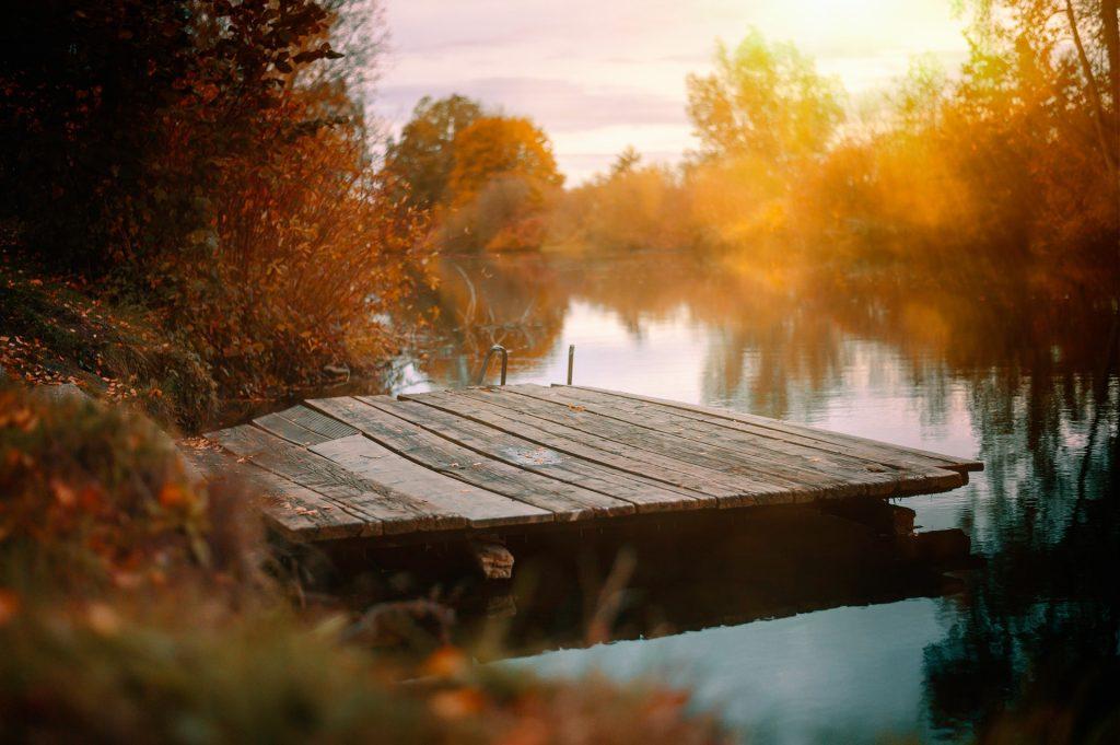 Een mooi, klein piertje aan een riviertje. De zond begint langzaam onder te gaan, wat zorgt voor het mooie oranje licht. Een perfecte plek om uit te rusten.