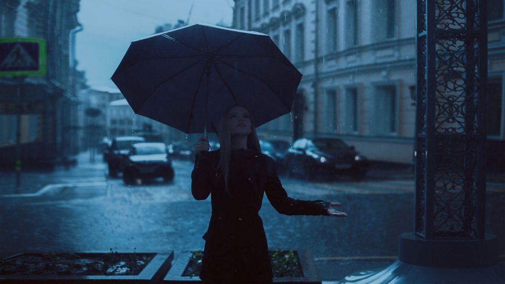 Een jonge, blonde vrouw geniet van de regen terwijl ze zelf lekker droog staat onder een paraplu. De stad lijkt op een mooie Franse stad, waar regen in de herfst normaal is. De foto is mooi bewerkt wat zorgt voor de blauwe achtergrond.