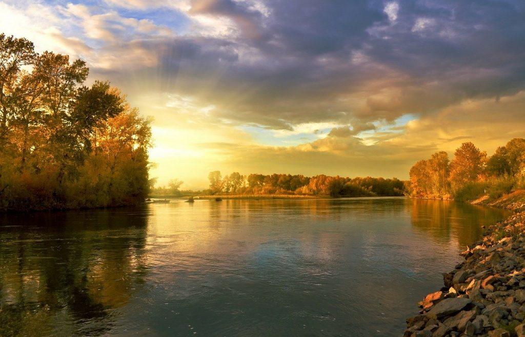 Terwijl de fotograaf op zijn ochtendwandeling was, stuitte hij op dit prachtige meer, terwijl de zon opkwam. Dat resulteerde in een voortreffelijke foto van het opkomende gele zonlicht dat gloeit over het blauwe meer-water.