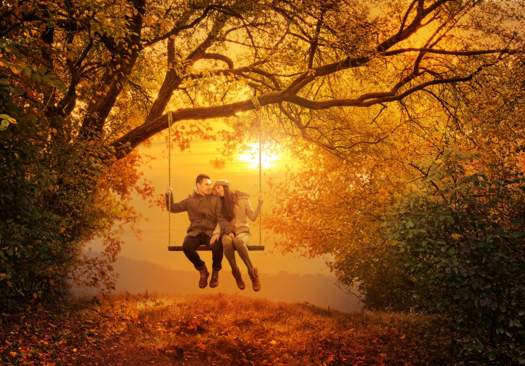 Een leuk koppel dat een romantisch moment heeft op een reusachtige schommel, met op de achtergrond een ver uitstrekkend landschap, terwijl de zon prachtig onder gaat. Het stel heeft een enorm romantisch moment. Het perfecte herfstmoment.