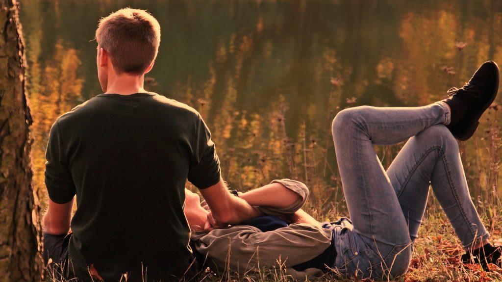 Een jonge man die een romantisch moment heeft met zijn vriendin aan een meer in de herfst. Ze nemen een pauze in een mooie middagwandeling terwijl de zon mooi op hen schijnt. De ideale herfstomstandigheden.