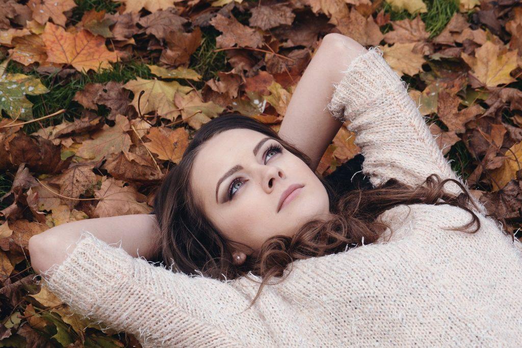 Een jonge dame ligt uit te rusten in de herfstbladeren. Ze heeft een wollen truitje aan en bruine haren. Ze ligt op de bruingekleurde esdoornbladeren. Een bijzonder herfstmoment.